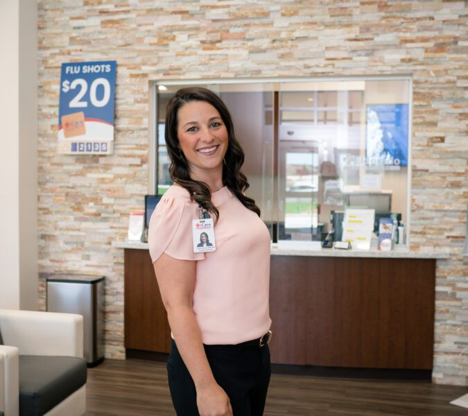 Woman with brown hair and pink shirt poses for headshot in lobby iCare Emergency Room & Urgent Care in Fort Worth, TX.