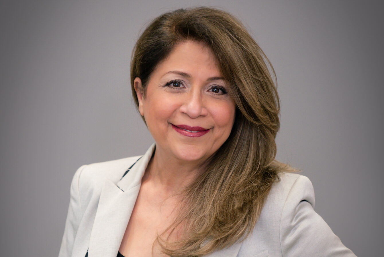 headshot of brown haired woman with gray blazer, gray background